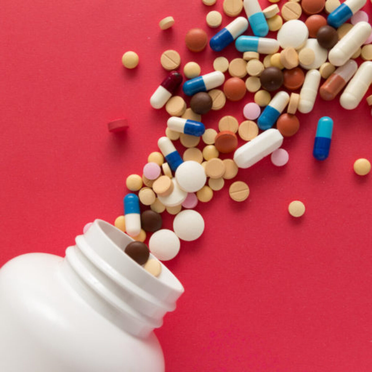 Group of assorted colorful tablets. Capsules spilling out of white bottle. Red background. Line, way course concept. (Group of assorted colorful tablets. Capsules spilling out of white bottle. Red background. Line, way course concept., ASCII, 117 comp